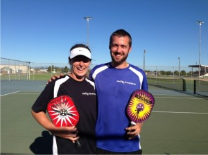 Wes Gabrielsen with female pickleball partner on the court  arm and arm holding MGS pickleball paddles