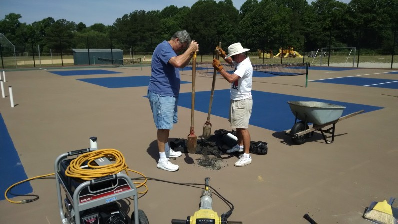 Hole diggers cleaning out holes for pickleball post sleeves