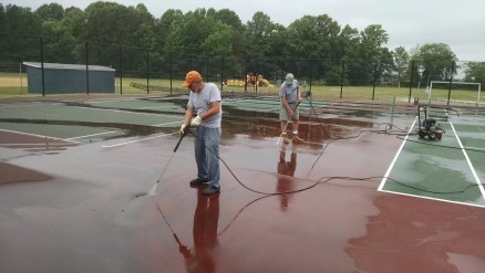 Pressure washing grime off the surface of court