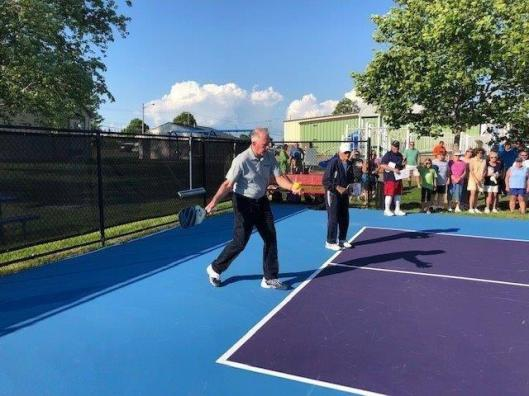 New York State Senator Michael H. Ranzenhofer making the first official serve on the Town of Riga's Pickleball Complex.